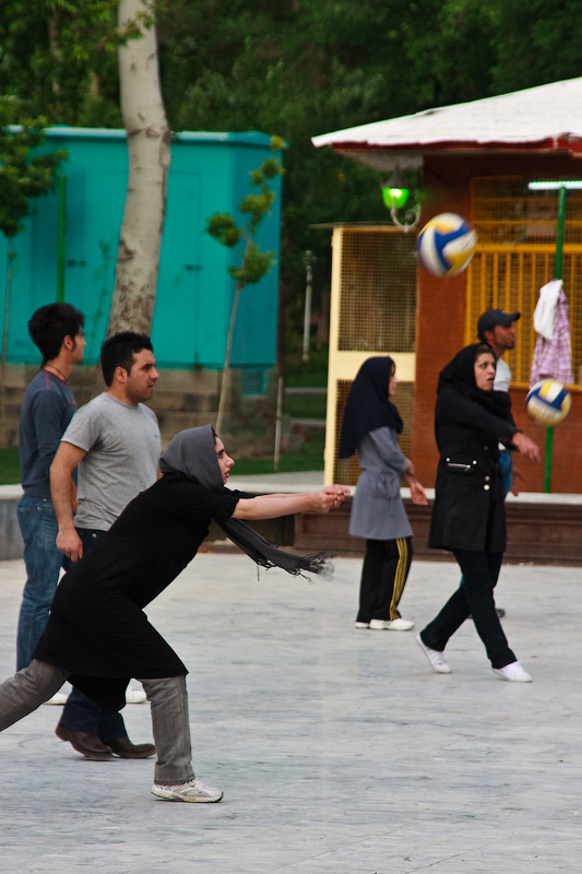 Парни и девушки играют в волейбол